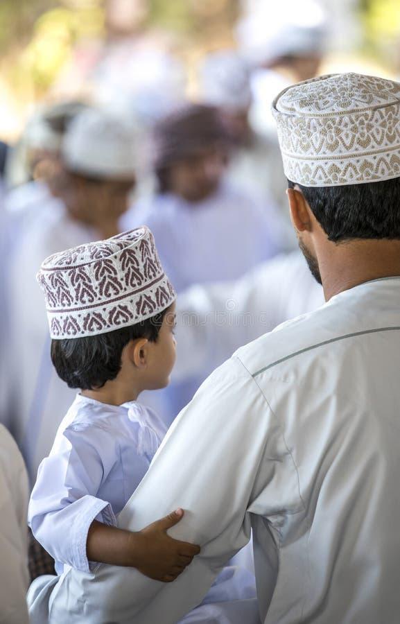 Homme omanais avec son fils à un marché photo libre de droits