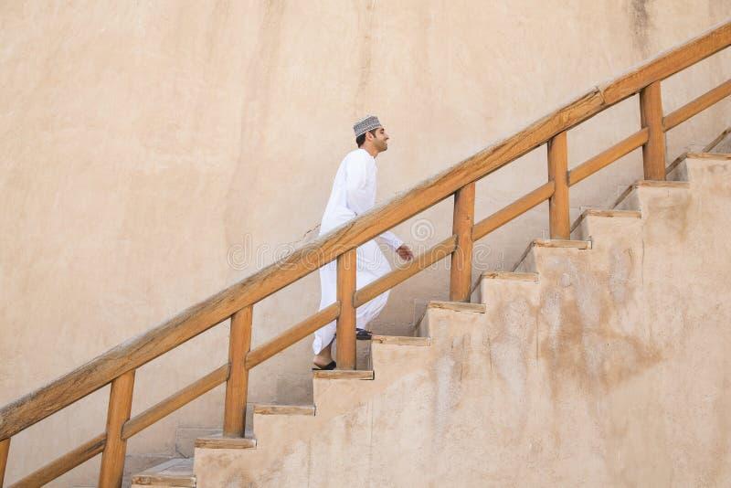 Homme omanais marchant vers le haut des escaliers dans le fort de Nizwa photo libre de droits