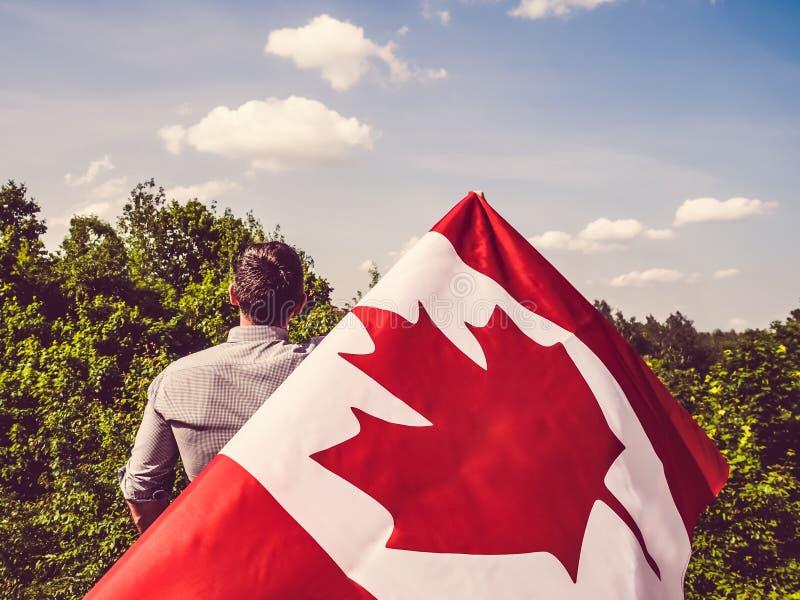 Homme ondulant un drapeau canadien Vacances nationales image stock