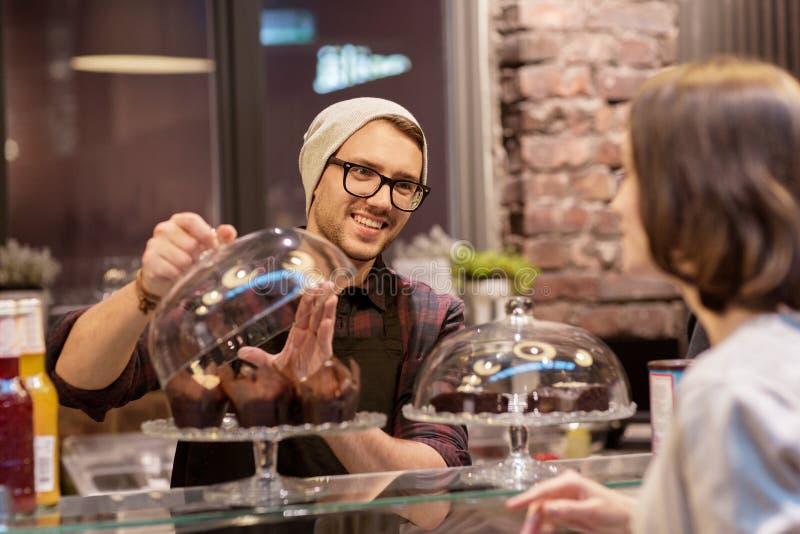 Homme ou barman avec des gâteaux servant le client au café photos stock