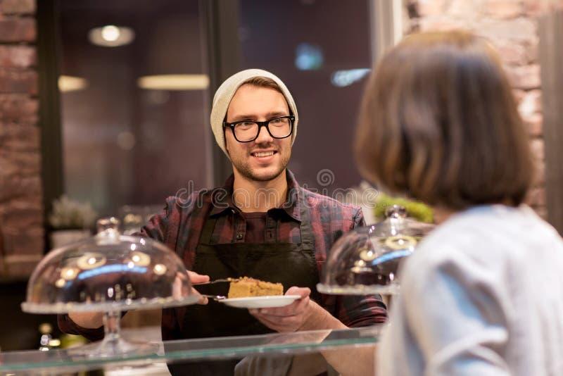 Homme ou barman avec des gâteaux servant le client au café image stock