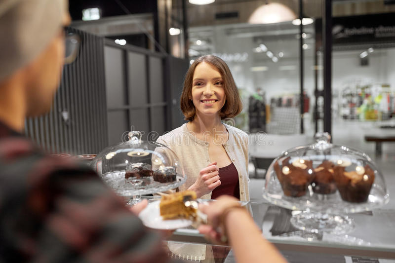 Homme ou barman avec le client de portion de gâteau au café image stock