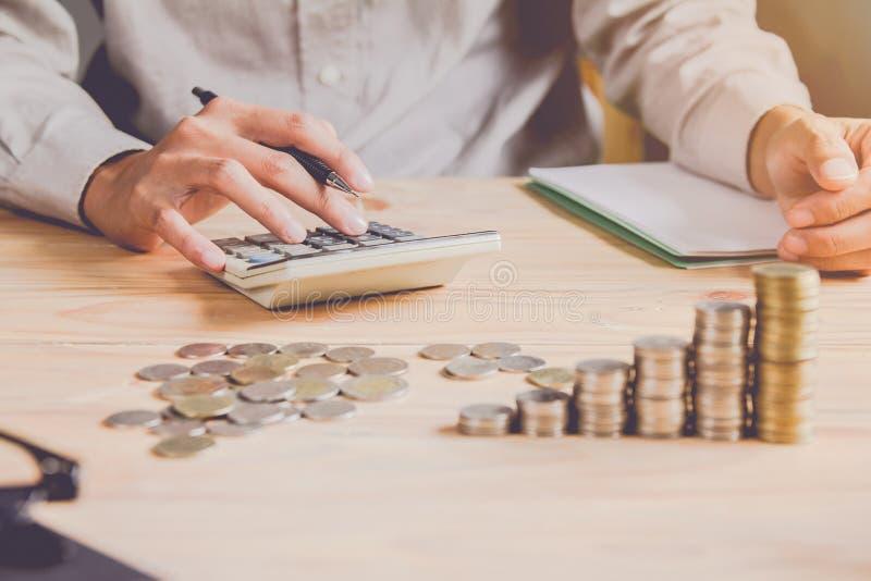 Homme ou comptable d'affaires dans le stylo de participation gris de chemise travaillant sur des comptes et ? l'aide de la calcul photos stock