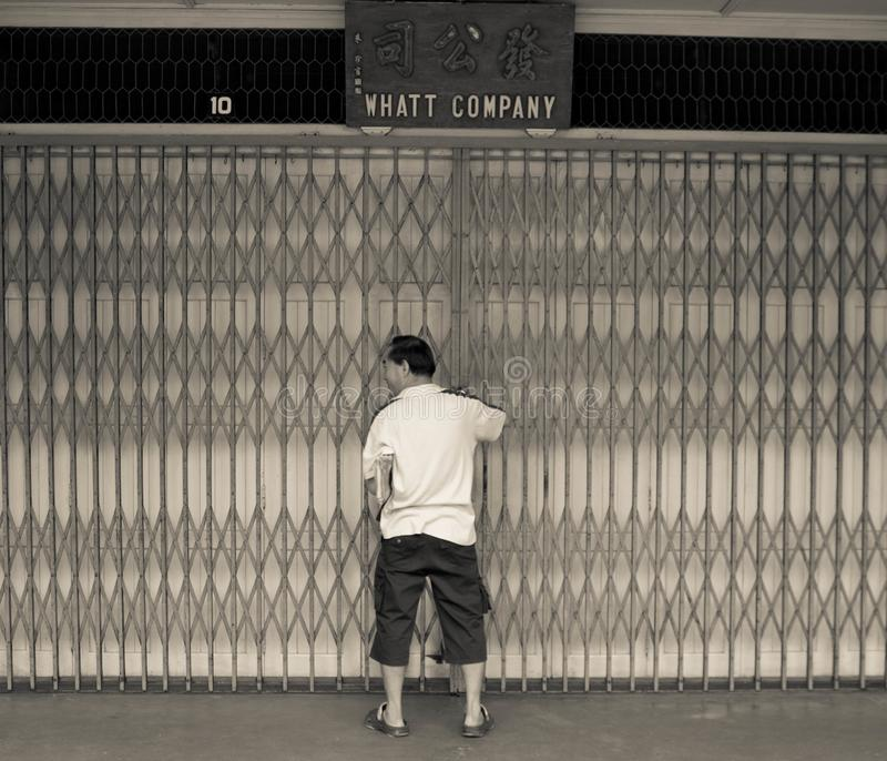 Homme ouvrant la porte en métal de sa maison de magasin sur la rue de Kuching, Malaisie image stock