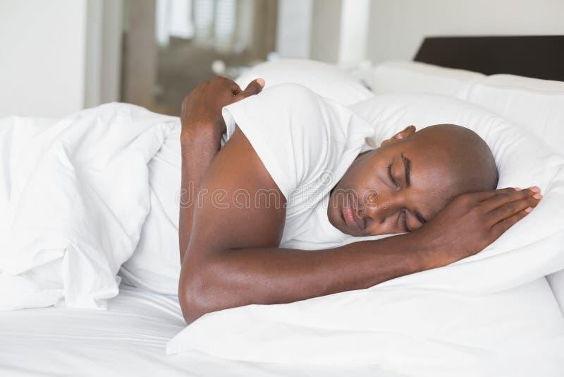 Homme paisible dormant dans le lit photographie stock libre de droits