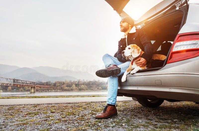 Homme pané dans des vêtements chauds situant avec le briquet dans le tronc de voiture Tra images stock
