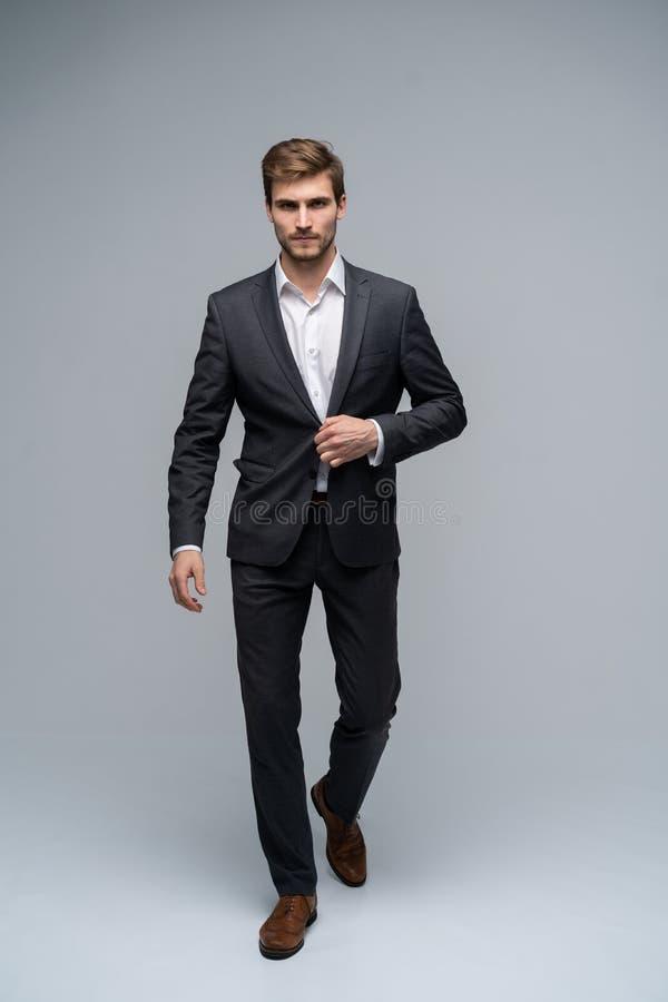 Homme parfait Intégral du jeune homme beau dans le plein costume boutonnant sa veste et regardant la caméra tout en se tenant photo stock