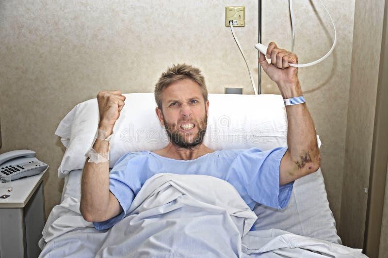 Homme patient fâché à la chambre d'hôpital se situant dans le sentiment de bouton d'appel d'infirmière de pressing de lit nerveux photographie stock