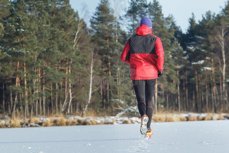 Homme pendant la course courante de traînée de sport en hiver extérieur image libre de droits
