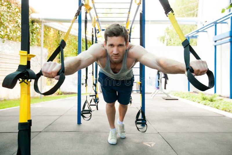 Homme pendant la séance d'entraînement avec des courroies de suspension sur la rue photos libres de droits