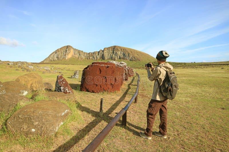 Homme photographiant les noeuds ou le chapeau supérieurs de la statue de Moai montrant au sol chez Ahu Tongariki, île de Pâque photo libre de droits