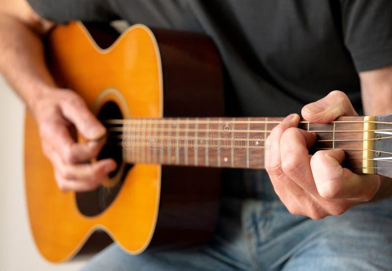 Homme pianotant une guitare acoustique images libres de droits