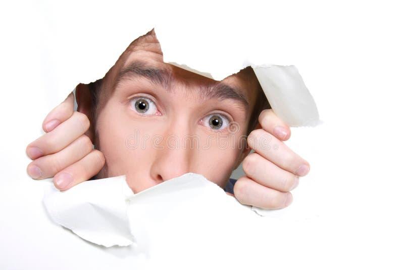 Homme piaulant par le trou sur le papier image stock
