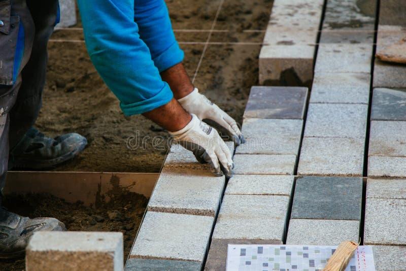 Homme plaçant des pierres de revêtement bétonné comme matériau de construction images stock