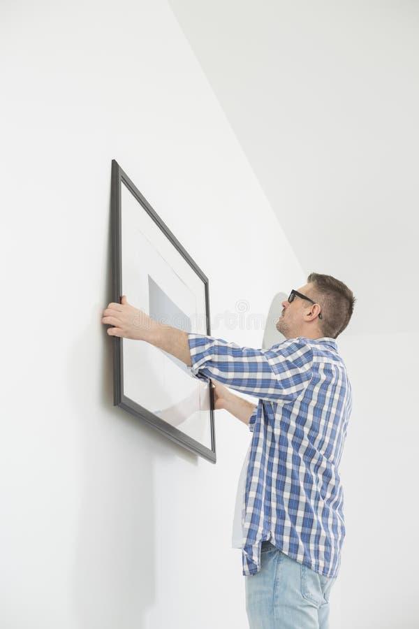 Homme plaçant le cadre de tableau sur le mur image stock