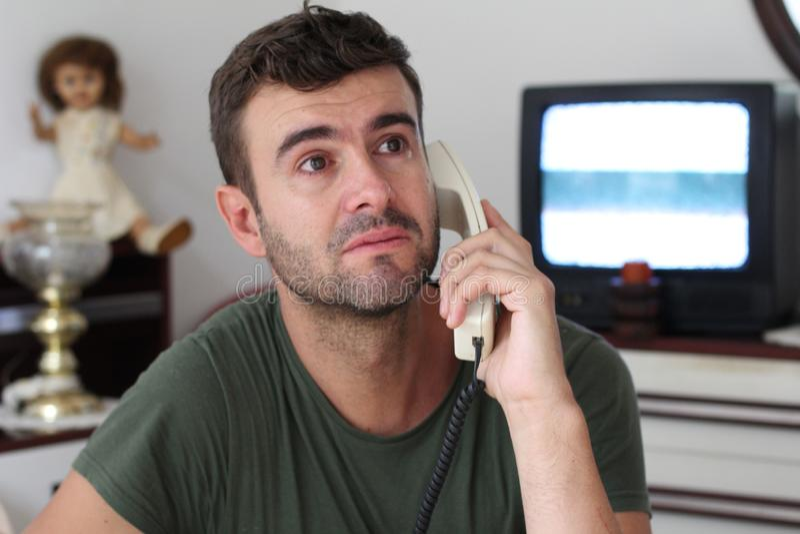 Homme pleurant à la maison pendant la conversation téléphonique photos stock