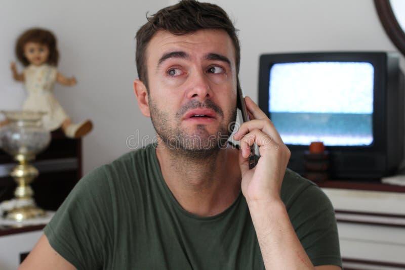 Homme pleurant à la maison pendant la conversation téléphonique photo stock