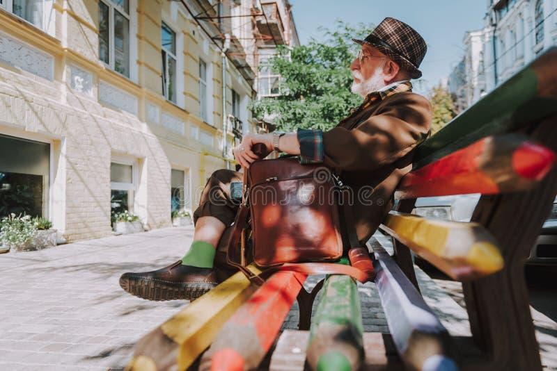 Homme plus âgé élégant s'asseyant sur un banc photographie stock libre de droits