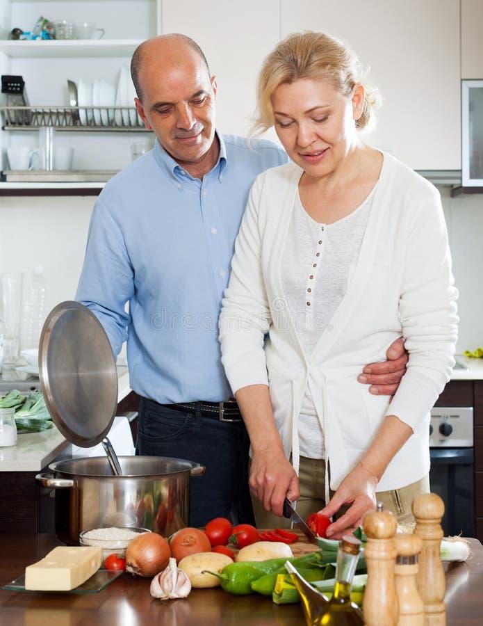 Homme plus âgé affectueux et épouse mûre faisant cuire des légumes photos stock