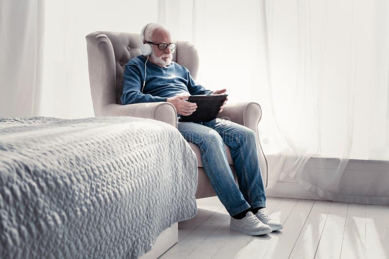 Homme plus âgé agréable appréciant la musique images stock