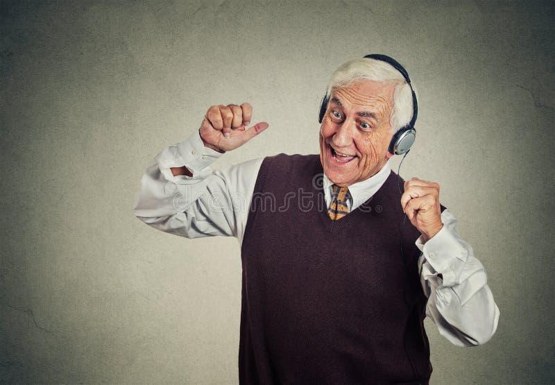 Homme plus âgé avec des écouteurs écoutant la radio appréciant la musique image libre de droits
