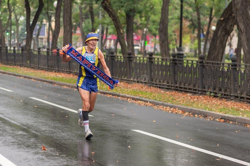 Homme plus âgé courant sur une rue de ville prenant la bannière de sa ville indigène Mariupol pendant la distance de 21 kilomètre image libre de droits