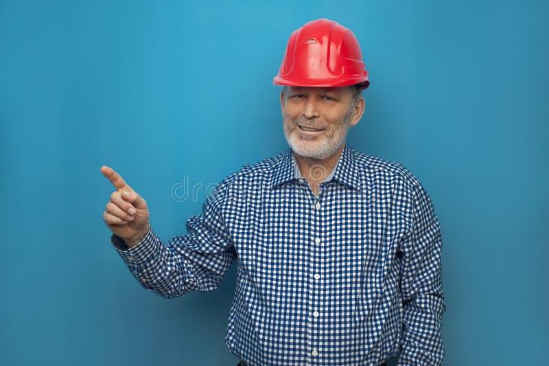 Homme plus âgé dans le casque rouge utilisant la chemise bleue photos stock