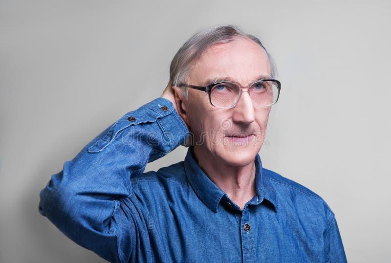 Homme plus âgé dans une chemise bleue de denim images stock