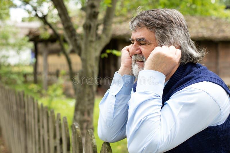 Homme plus âgé devant sa vieille maison image stock