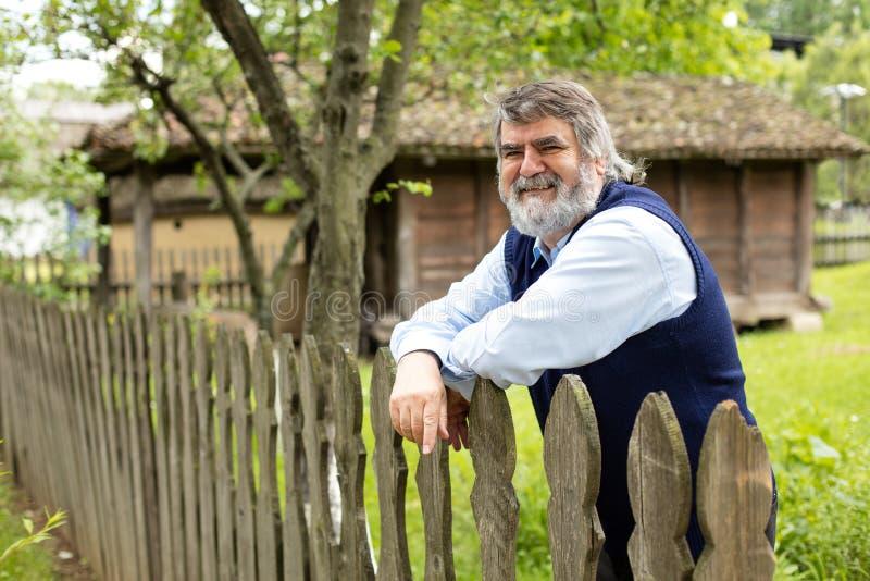 Homme plus âgé devant sa vieille maison images libres de droits