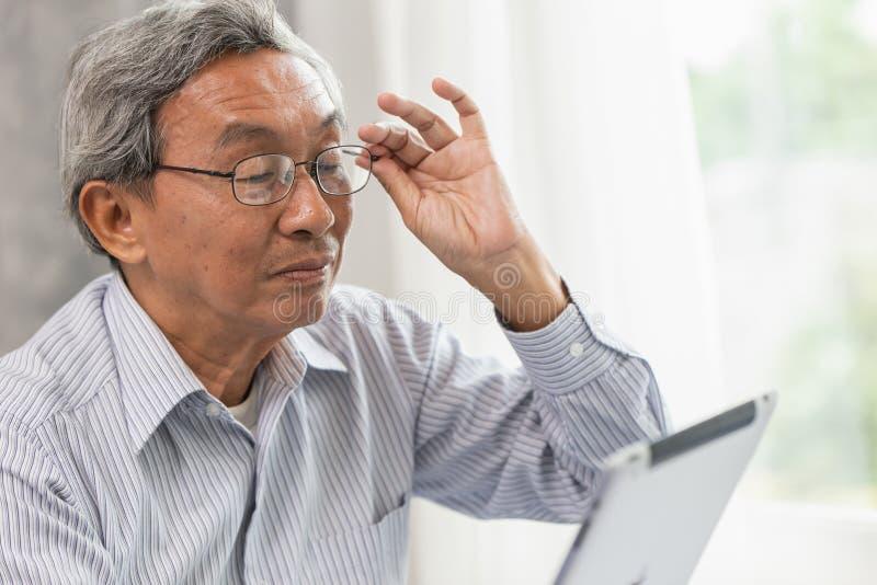 homme plus âgé en verre vieil heureux utilisant regarder l'écran de Tablette image libre de droits