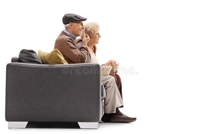 Homme plus âgé et femme s'asseyant sur un sofa et mangeant du maïs éclaté image libre de droits