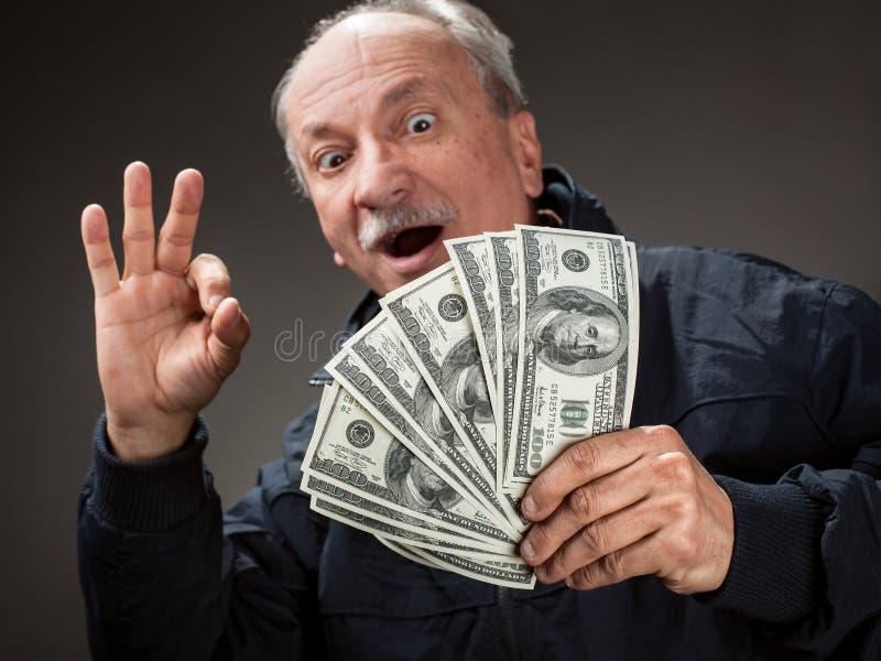 Homme plus âgé heureux affichant le ventilateur de l'argent photo libre de droits