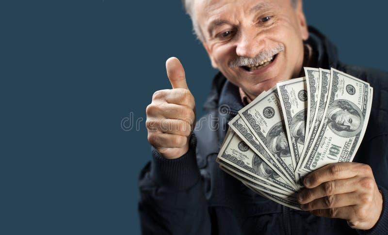 Homme plus âgé heureux affichant le ventilateur de l'argent photographie stock