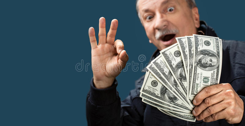 Homme plus âgé heureux affichant le ventilateur de l'argent photographie stock libre de droits