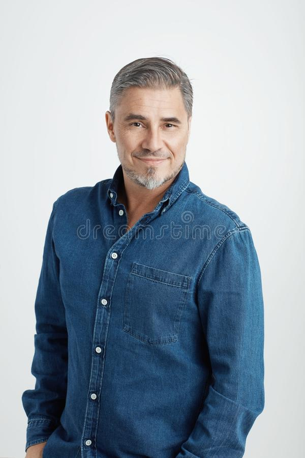 Homme plus âgé heureux dans le sourire occasionnel de chemise de jeans photographie stock