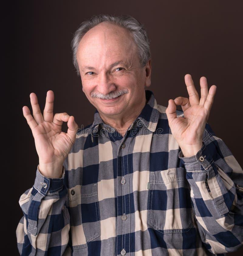 Homme plus âgé heureux montrant le signe correct photos stock