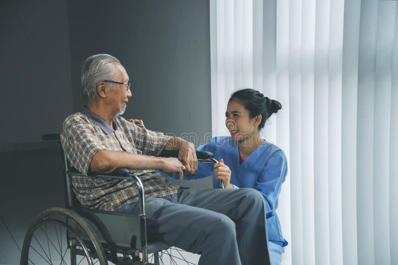 Homme plus âgé heureux parlant avec son infirmière photos stock