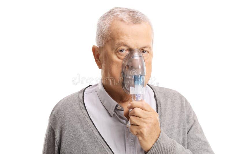 Homme plus âgé inhalant avec un masque d'isolement sur le fond blanc images stock