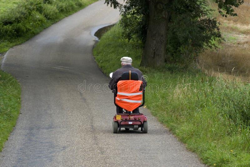 Homme plus âgé montant le scooter mobile, Pays-Bas image stock