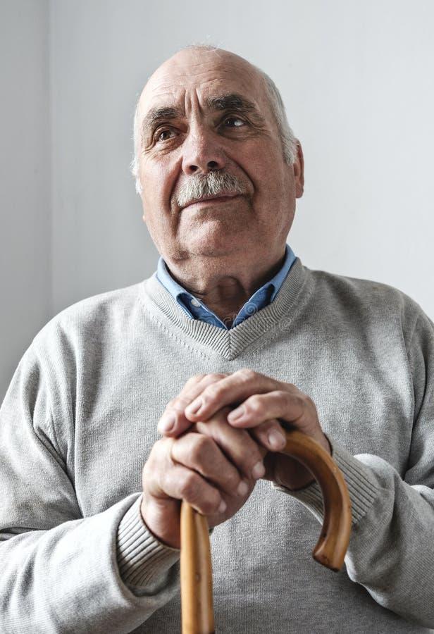 Homme plus âgé nostalgique avec une canne ou un bâton de marche images stock