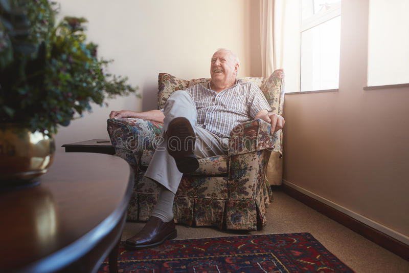 Homme plus âgé s'asseyant sur la chaise de bras à la maison de vieillesse photographie stock