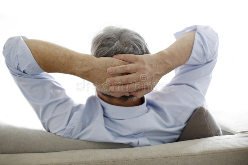 Homme plus âgé s'asseyant sur la détente de sofa photo stock