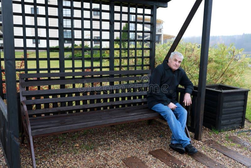 Homme plus âgé s'asseyant sur le banc images stock