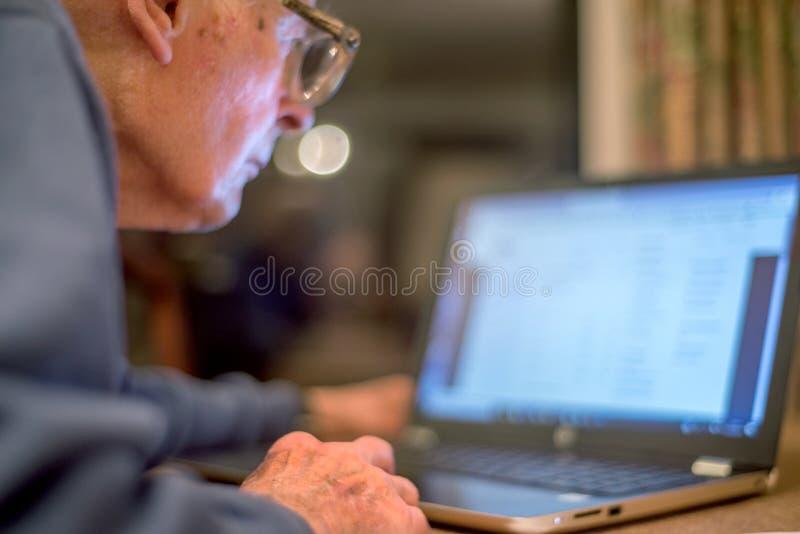 Homme plus âgé se renseignant sur l'Internet, utilisant un ordinateur portable pour vérifier ses portefeuilles d'actions, le Hamp image stock