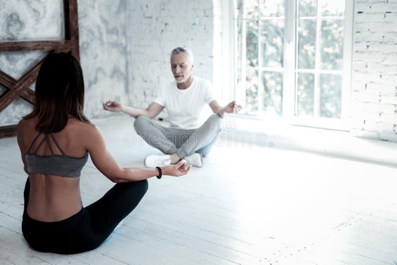 Homme plus âgé suivant la classe de yoga et méditant photo libre de droits