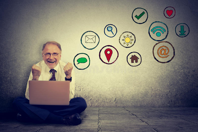 Homme plus âgé travaillant sur l'ordinateur utilisant l'application sociale de media photographie stock