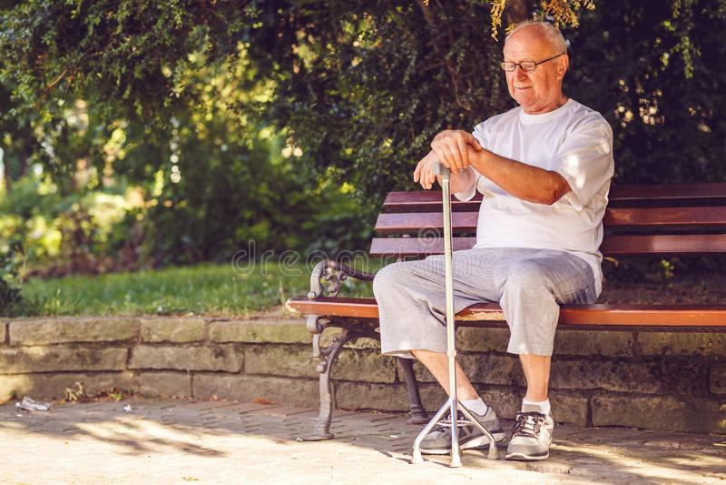 Homme plus âgé triste avec son bâton de marche se reposant sur le banc photo stock