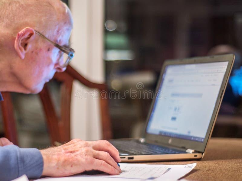 Homme plus âgé utilisant l'ordinateur pour vérifier sa situation financière, Hampshire, Angleterre, U k photo stock