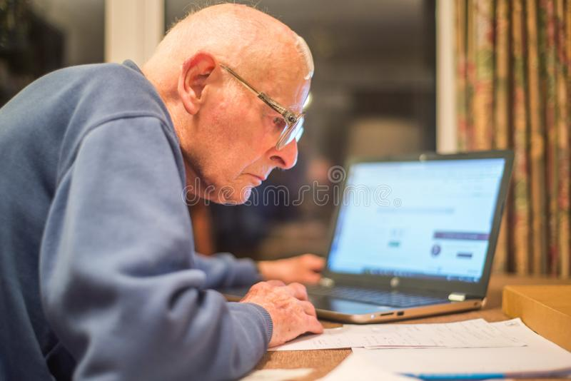 Homme plus âgé utilisant un ordinateur portable pour vérifier des portefeuilles d'actions, Hampshire, Angleterre, U k photo libre de droits